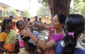 Volunteer giving oral medicine to kids for worms.