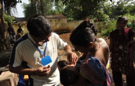 Volunteer Ashish giving oral medicine to a child.