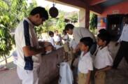 Volunteers administering medicine to children
