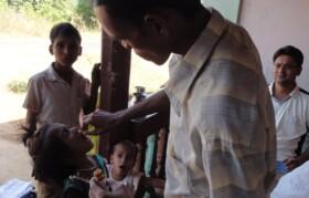 Volunteer administering oral medication to children.