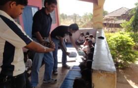 Volunteers distributing school supplies to children with the help of school teachers.