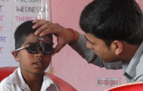 Child being tested by Optometrist Dheeraj for reading for any refractive error. Majority of children had good reading eye, however, deficient of Vitamin A & D.