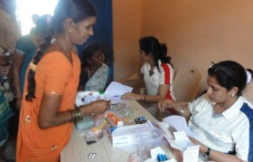 Along with check-up, medicines were also distributed to patients. Volunteer explaining dosage of medicine to patient.