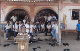Team posing for group picture in front of the house if village leader.
