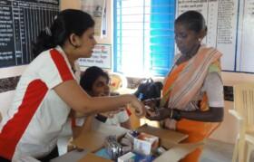 Volunteers explaining medicine prescription to patient.