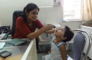 Child being administered dosage of Suvarna Prashan Sanskar