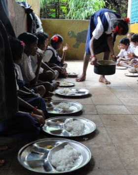 Kids help serve themselves cooked food.