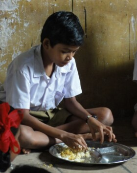 A boy enjoying the the changes to the meal.