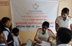 Another team of doctor and assistant checking kids in presence of sir from the school
