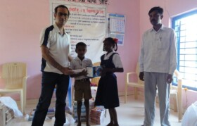 Suhrid team member handing over new education material such as charts/globe to kids