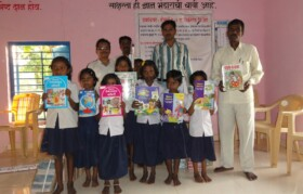 Kids posing with books along with village senior - Dattu Bahiram