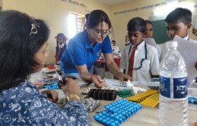 Volunteers explaining medicines to kids - and sirs so that they can monitor